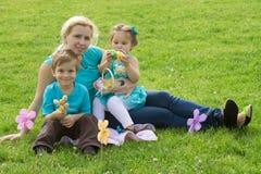 Mutter und kleiner Junge und Mädchen im grünen Gras Lizenzfreie Stockfotos