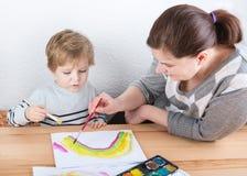 Mutter und kleiner Junge von zwei Jahren Spaßmalerei habend Lizenzfreies Stockfoto