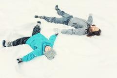 Mutter und kleiner Sohn, die im Schnee spielen stockbilder