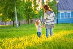 Mutter und kleiner sonniger Park der Tochter im Frühjahr lizenzfreies stockbild