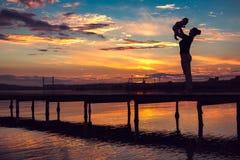 Mutter und kleines Baby, die Spaß bei Sonnenuntergang haben Stockfoto
