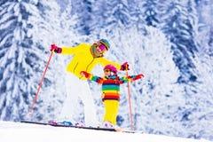 Mutter und kleines Mädchen, die lernen Ski zu fahren stockfotografie