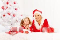 Mutter und kleines Mädchen legen unter Weihnachtsbaum Lizenzfreie Stockfotos