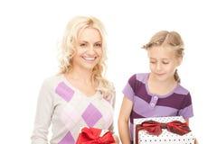 Mutter und kleines Mädchen mit Geschenken Lizenzfreie Stockfotos
