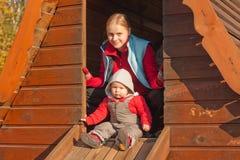 Mutter- und Kleinkindmädchen sitzen im kleinen Haus auf Winkel des Leistungshebels Stockfotografie