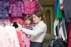 Mutter und Mädchen am Kleidungsshop Stockbilder