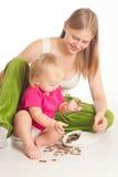 Mutter- und Mädchenspiel mit Münzen Stockfotografie