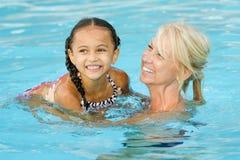 Mutter- und Mischrassemädchen, das im Pool spielt Lizenzfreie Stockfotos