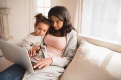 Mutter und nette kleine Tochter, die zusammen auf Couch sitzen und Laptop verwenden Lizenzfreie Stockbilder