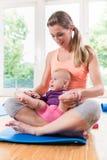 Mutter und neugeborenes Baby, die zusammen im Babykurs spielen Stockfotos
