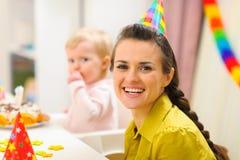 Mutter und Schätzchen, die Geburtstagkuchen im Hintergrund essen lizenzfreies stockbild