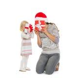 Mutter und Schätzchen, die hinter Weihnachtsgeschenkkästen sich verstecken Stockfoto