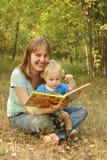 Mutter- und Schätzchenlesebuch in der Natur Lizenzfreie Stockfotografie