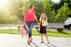 Mutter und Schulmädchen des Grundschulehändchenhaltens Stockbild