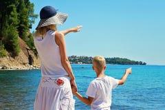 Mutter und Sohn auf dem Strand Frauen- und Jungensohn vor dem Meer, die weg, aktiven Sommerferienferien, Familienreisefoto zeigen Stockbild