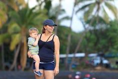 Mutter und Sohn auf einem hawaiischen schwarzen Sand setzen auf den Strand Stockbilder