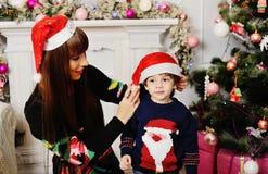 Mutter und Sohn auf einem Hintergrund des Weihnachtsbaums lizenzfreies stockbild