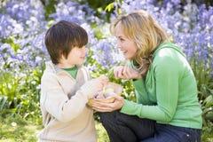 Mutter und Sohn auf Ostern, das nach Eiern sucht Stockbild