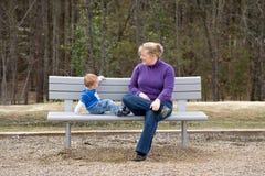 Mutter und Sohn auf Parkbank stockfoto