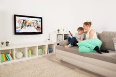 Mutter-und Sohn-aufpassendes Fernsehen zu Hause lizenzfreie stockfotografie