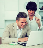 Mutter und Sohn betrachten Software auf Laptop Stockbild
