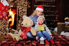 Mutter und Sohn in den Kappen von Santa Claus auf einem Hintergrund der gemütliche Kamin Lizenzfreies Stockbild