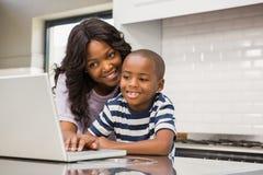 Mutter und Sohn, der Laptop verwendet Stockbilder