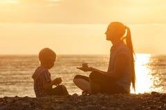 Mutter und Sohn, die auf dem Strand mit Steinen spielen Sonnenuntergangzeit, Schattenbilder Lizenzfreie Stockbilder