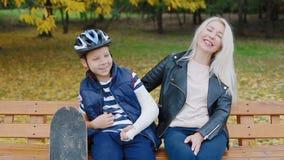 Mutter und Sohn, die auf der Bank im Park sitzen stock video footage