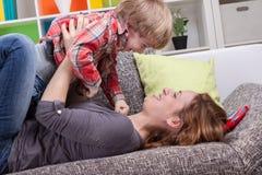 Mutter und Sohn, die auf der Couch spielen Stockbilder