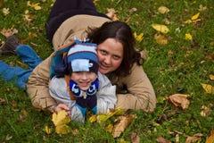 Mutter und Sohn, die auf Gras liegen Lizenzfreie Stockfotos