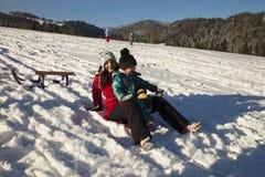 Mutter und Sohn, die auf Schnee rodeln Stockfotografie