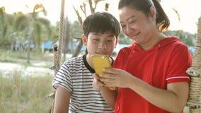 Mutter und Sohn, die auf Schwingen schwingen und am Handy zusammen mit Lächelngesicht aufpassen stock footage