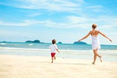 Mutter und Sohn, die auf Strand laufen Lizenzfreies Stockfoto