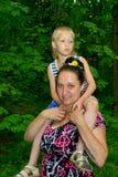 Mutter und Sohn, die in den grünen Wald gehen Lizenzfreies Stockfoto
