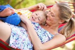 Mutter und Sohn, die in der Hängematte sich entspannen Lizenzfreie Stockbilder