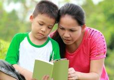 Mutter und Sohn, die ein Buch lesen Stockbild