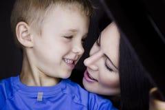 Mutter und Sohn, die an einander lächeln Stockbilder