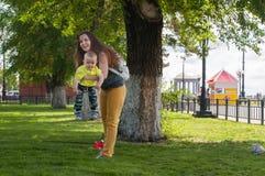 Mutter und Sohn, die im Park nahe dem Baum auf seinen Händen spielen Lizenzfreie Stockbilder