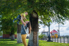 Mutter und Sohn, die im Park nahe dem Baum auf seinen Händen spielen Lizenzfreie Stockfotografie