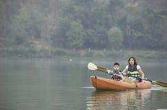 Mutter und Sohn, die im Reservoir Kayak fahren stockbild