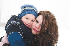 Mutter und Sohn, die im Schnee spielen Lizenzfreie Stockfotos