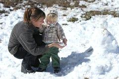 Mutter und Sohn, die im Schnee spielen und einen Schneemann bulding Lizenzfreie Stockbilder