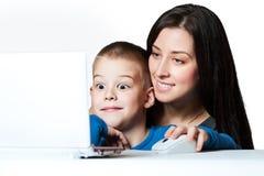 Mutter und Sohn, die am Laptopbildschirm slooking sind Stockfotografie