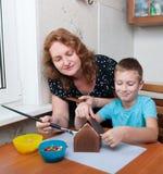 Mutter und Sohn, die Lebkuchenhaus bilden Stockbilder