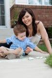 Mutter und Sohn, die mit Bürgersteig-Kreide spielen Lizenzfreie Stockfotografie
