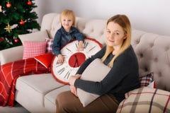 Mutter und Sohn, die nahe dem Weihnachtsbaum sitzen Stockbild