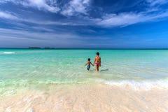 Mutter und Sohn, die in Richtung zum weißen sandigen kubanischen Strand in Cayo-Cocos gehen Lizenzfreie Stockfotografie