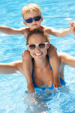 Mutter und Sohn, die Spaß im Swimmingpool haben lizenzfreies stockbild