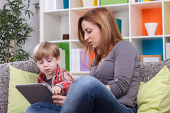 Mutter und Sohn, die Tablette zeigen Stockbild